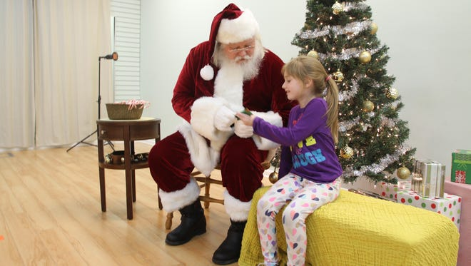 Bailey Rottach, 6, of Howell accepts a gift-wrapped candy cane from Santa at Leaps and Bounds Therapy Services in Howell Friday. Her mom, Ashley Rottach (not pictured) said Bailey, who is on the autism spectrum, would likely have trouble going to see Santa in a crowded mall and the event she attended focuses on kids who are sensory sensitive.