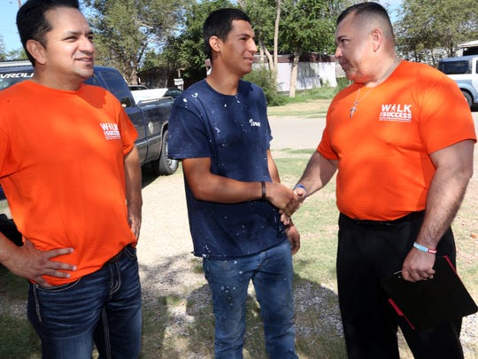Socorro High School Principal Josh Tovar, right, and Socorro Independent School District Superintendent Jose Espinoza, left, meet with Israel Rubio, 18, who left high school after his junior year, outside his Socorro home Saturday. The young man agreed to meet with Tovar on Monday morning to discuss returning to school.