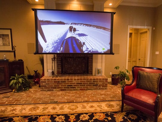 The living room of a home with a drop-down projection screen, part  of a high-end home theater system by Electronics Professionals in Lafayette