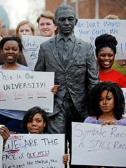 Students hold signs while posing for a photo during a gathering in front of the James Meredith statue at the University of Mississippi in Oxford.