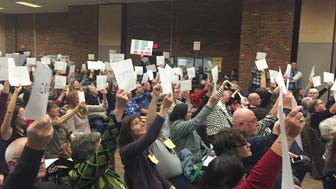 Attendees of a citizens' town hall held up pieces of paper with their ZIP code written on them, to show they are members of the 4th Congressional District in New Jersey, which Rep. Chris Smith oversees.