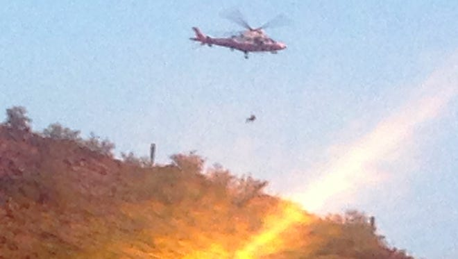 A man is airlifted by helicopter from the Piestewa Peak area.