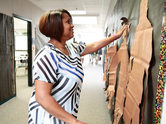 Kimberlyn Slagle adjusts silhouettes that her English students designed as part of a unit on Shakespeare. Slagle incorporates many hands-on activities into her lessons.