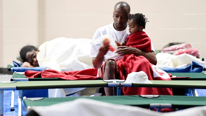 "Vernon Pillar holds his son Dukuan, 2, oh his lap while Shanta Jasper tries to catch some sleep in the background at a Red Cross shelter set up at First Baptist Church on Whites Creek Pike in Joelton, Friday, Sept. 1, 2017. They  evacuated from the Lewis Street Apartments. ""Dumpsters were floating from the back to the front. As we walked out the water was up to our thighs,"" Pillar said."