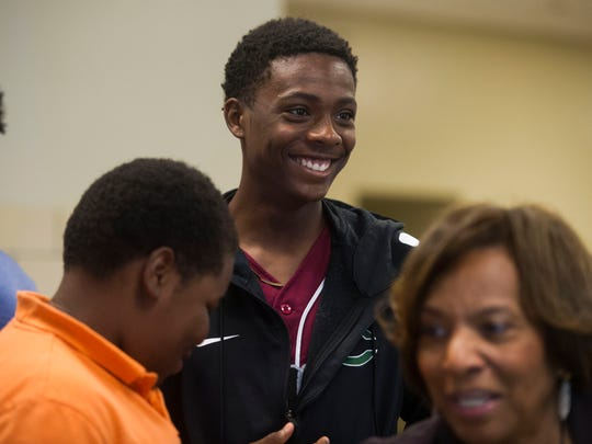 Trey Prater, 16, smiles with friends while signing-in at the Save our Sons Summit II event at Pellissippi State Community College's Magnolia campus on Friday, June 30, 2017. Save Our Sons works with the community to address gaps in opportunity and to end violence-related deaths among boys and young men of color.