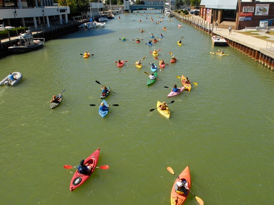 Participants head up the Black River, Sunday, Sept 8, during the Paddle and Pour event in Port Huron.