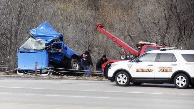 Crews remove the wreckage of a truck involved in a rollover on I-229 Tuesday near 10th Street.