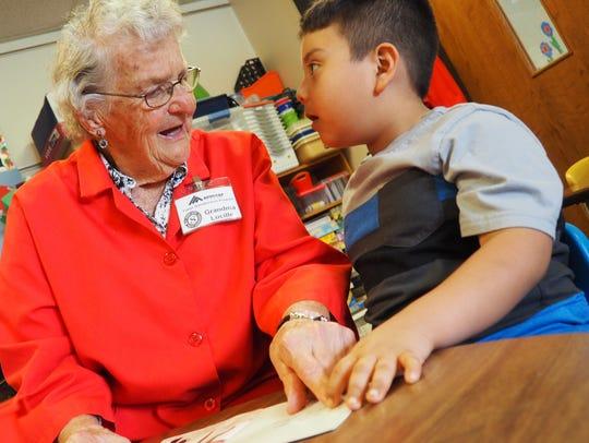 """""""Grandma"""" Lucille Wuest helps kindergartner Eduardo"""