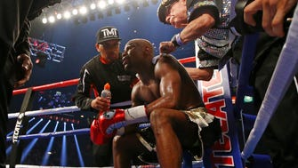 May 2, 2015; Las Vegas, NV, USA; Floyd Mayweather Jr is tended to by trainers as he sits on the stool in his corner between rounds against Manny Pacquiao during a boxing fight at the MGM Grand Garden Arena. Mandatory Credit: Mark J. Rebilas-USA TODAY Sports