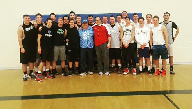 Cardinal Mooney alumni pose with boys basketball coach Mike McAndrews.