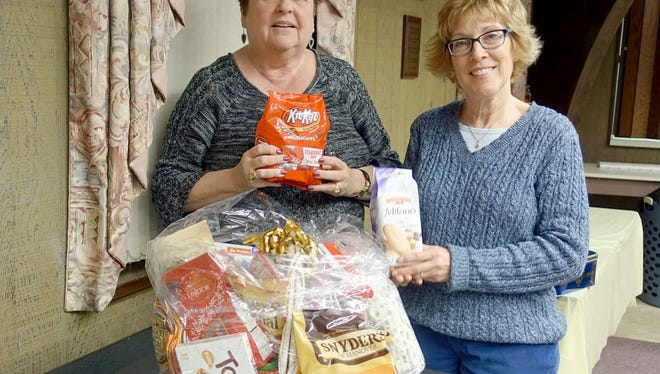 """Norene Ritter (left) and Judy Bonato, members of the Woman's Club of Vineland, prepare an """"appreciation basket"""" for the volunteers at Vineland Public Library."""