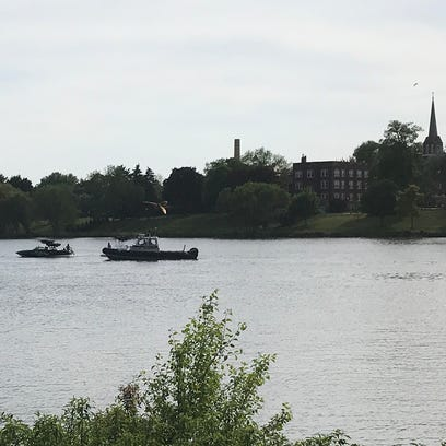 A boat is towed to the shore of the Fox River in De