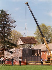 In this April 22, 1998 photo, the attic study of the home of the late Lyman Beecher is lifted off of its colonial post and beam foundation on the Foreman School campus in Litchfield, Conn. Taken apart and stored in pieces, the house where Harriet Beecher Stowe grew up is for sale on eBay, with an asking price of $400,000. Museums passed on the building, and the owner went to the online auction site after finding no takers on Craigslist. (Patrick Raycraft/The Courant via AP)