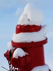 A fire hydrant is topped with snow Sunday in Wausau, where wind chills already had dipped well below zero.