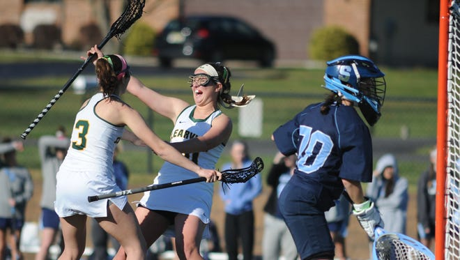 Clearview's Vikki Ciara (3) and Kasey Diodati (20) celebrate a goal on Wednesday. The Pioneers beat Shawnee 13-10, the program's first-ever victory over the Renegades.