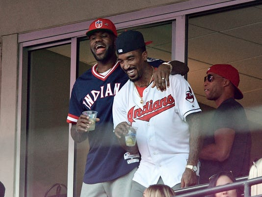 Cleveland Cavaliers' LeBron James, left, stands with J.R. Smith during the sixth inning of Game 2 of a baseball American League Division Series between the Cleveland Indians and the Boston Red Sox, Friday, Oct. 7, 2016, in Cleveland. (AP Photo/David Dermer)