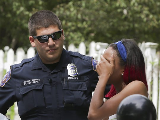 IMPD officer James Perry speaks with a woman after