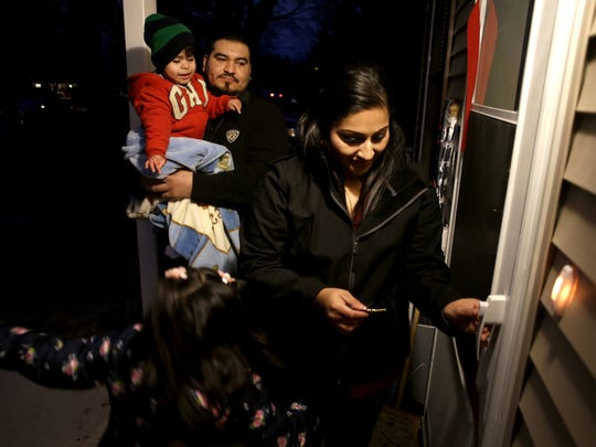 Berenice Sierra prepares to unlock the front door to her new home with her husband Jose and two children Neomi and Christopher Tuesday, Dec. 15, 2015, in Appleton, Wis. The Sierra family's home was the 200th homebuyer program home from the Greater Fox Cities Area Habitat for Humanity.