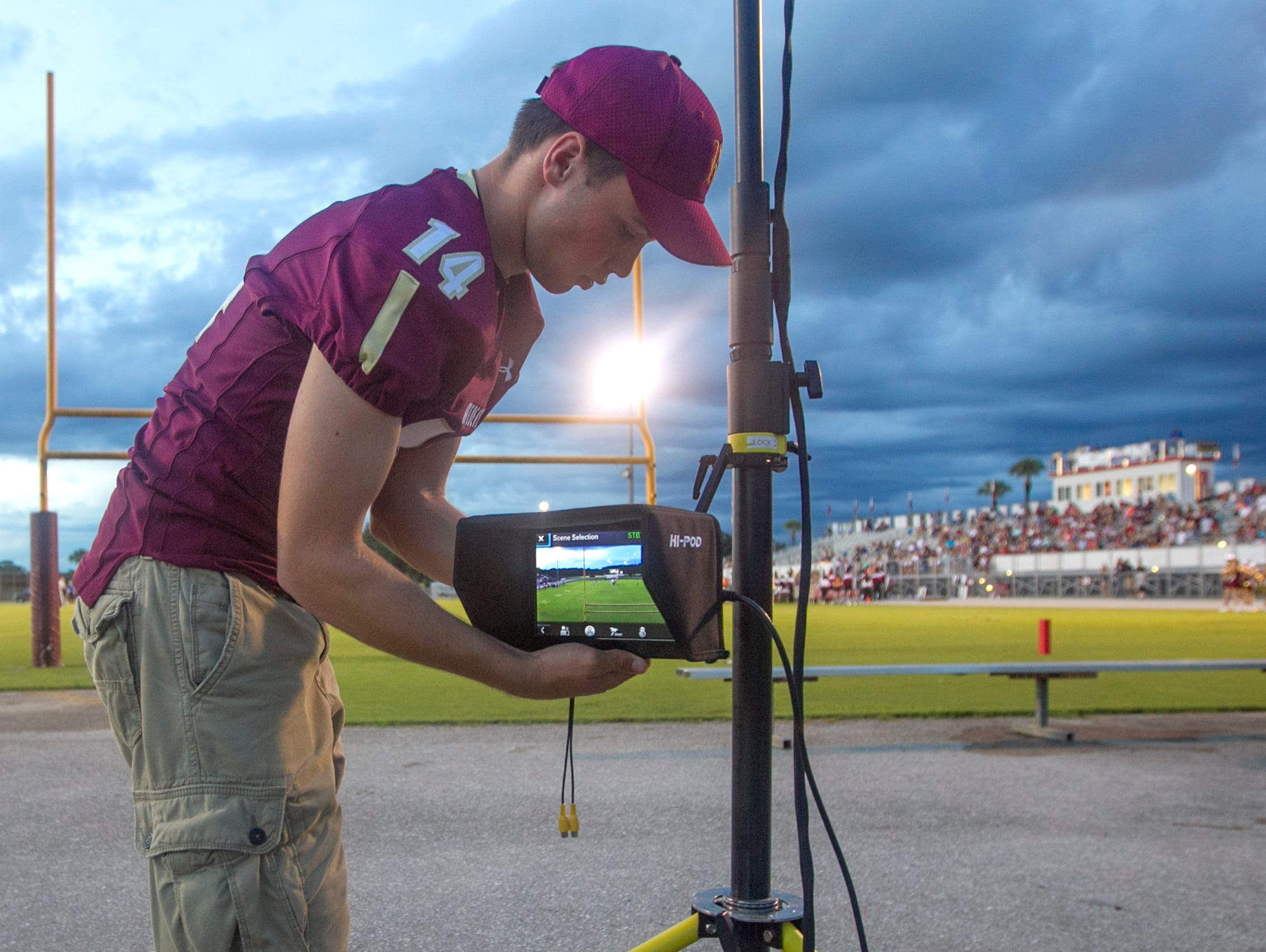 Cole Baer,16, sets up Riverdale's end-zone camera Friday, September 25 in Fort Myers. Baer volunteered to man the remote-controlled set-up after a torn ACL ended his football season.
