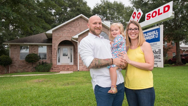 First-time homebuyers Jaime and David Gibbs pose with their daughter, Emma, 2, outside of their new home in Pace on Tuesday, Aug. 8, 2017.
