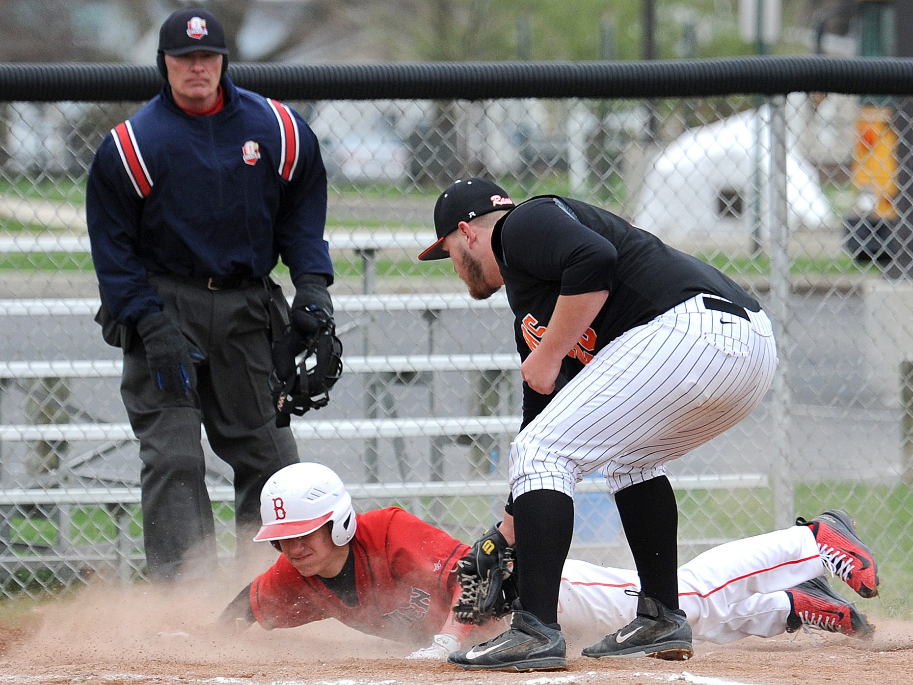 Bucyrus' Jesse Heinle slides on home base as Upper Sandusky's pitcher, Cody Gabriel, attempts to tag Heinle out during their game Wednesday evening.