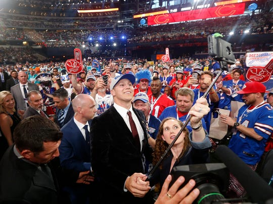 Wyoming's Josh Allen, center, takes a selfie of himself with Buffalo Bills fans after being selected by the team during the first round of the NFL Draft.