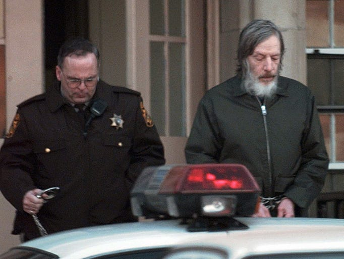 John e du pont is escorted to a waiting sheriff s car by a delaware