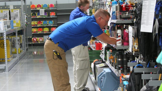 Nathan Grummert and Nathan Noerenberg, back, work in the new Walmart sporting goods department to make display items look sharp.