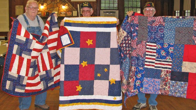 Bill Barnett, left, U.S. Army veteran of Vietnam; Dean Burnette, center, U.S. Army veterans of World War II and Ray Potze, U.S. Army veteans of Vietnam display quilts recently awarded to them by the Crooked Creek Quilt Guild. They were recommended by Yellville American Legion Post 61. The quilts were presented by Legion and guild member Annie Rogers and guild president Maddie Kiefer.
