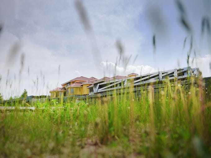 Grass is over grown at a seemingly-abandoned mansion