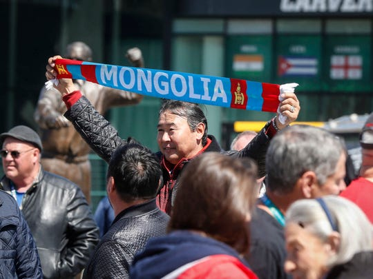 Enhkee Ulzii holds up a Mongolian banner outside of Carver Hawkeye Arena during the 2018 Wrestling World Cup in Iowa City on Saturday, April 7, 2018.