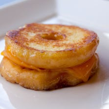 The Grilled Cheese Doughnut's cheddar on a glazed doughnut is one of many off-beat and familiar grilled cheese sandwiches at soon-to-open Tom+Chee in Northwestside.