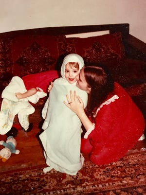 Abbey Doyle with her mom Bev Brown (twin sister Sarah Spurgeon is hiding underneath her blanket on the couch.)