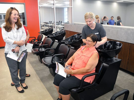 Cosmetology instructor Jessica Kenner, right, demonstrates the shampoo bowls to Roxann Preston in the cosmetology lab of the new Career Education Center during a tour Tuesday.