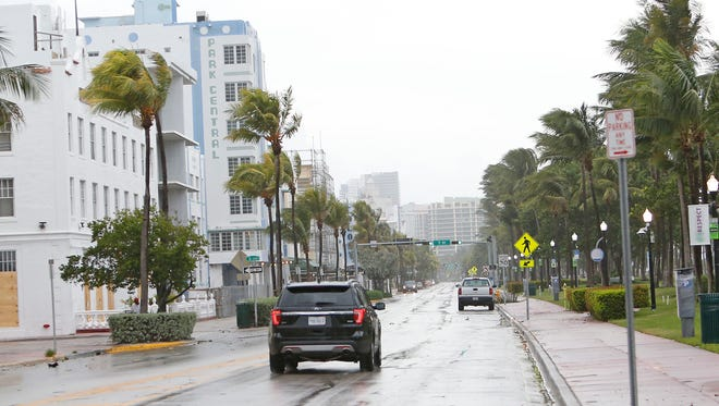A vehicle drives down an empty Ocean Drive on South Beach as the outer bands of Hurricane Irma reached South Florida early Sept. 9, 2017 in Miami.