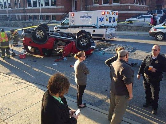 Emergency personnel survey the scene of a car crash