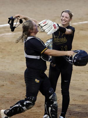 Louisa-Muscatine High School's Hailey Sanders (11) celebrates their Class 2A regional final victory over Wilton with catcher Morgan Stecher, Monday July 20, 2020 at L-M High School in Letts.