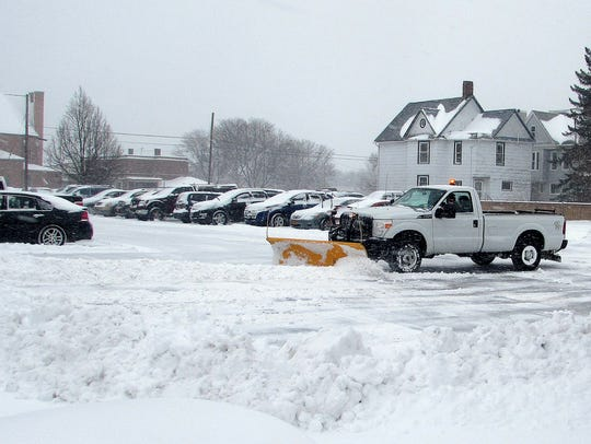 A pickup truck plows snow out of a parking lot near