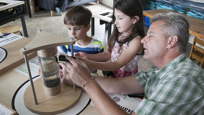 Austin Konz, 5, of Portland, Oregon, left, and Maddy Konz, 7, of Folsom, California, listen to Above and Beyond Children's Museum Executive Director Jeff Mehn, right, describe nanoparticles to them at a new display Wednesday, July 1, in Sheboygan.