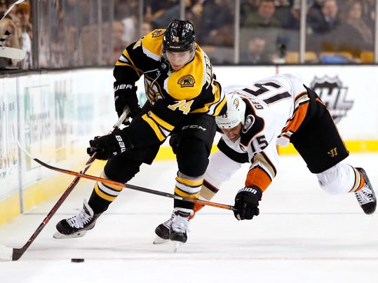 Anaheim Ducks' Ryan Getzlaf (15) tries to stop Boston Bruins' Jake DeBrusk during the second period of an NHL hockey game Tuesday, Jan. 30, 2018, in Boston. (AP Photo/Winslow Townson)