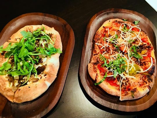 Flatbread selections at The Cave Bistro & Wine Bar include duck confit and goat cheese, left, and roasted heirloom tomato.