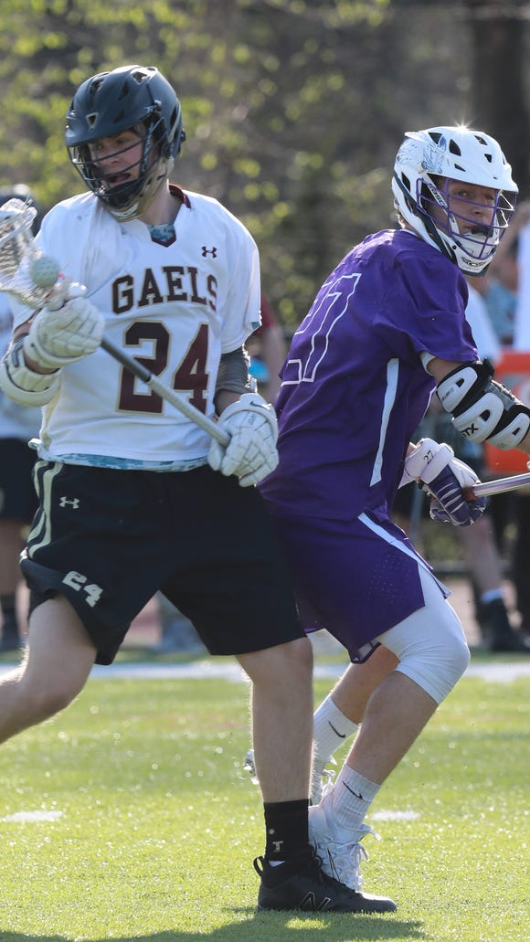 John Jay's Thor Acamec (27) guards Iona Prep's John Schreiber (24) during boys lacrosse game at Iona Prep in New Rochelle on May 1, 2018. John Jay defeats Iona Prep 6- 2.