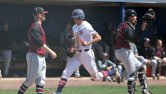 Shippensburg's Cash Gladfelter, center, scores a run in the first inning of the Red Raiders' game against Lock Haven.