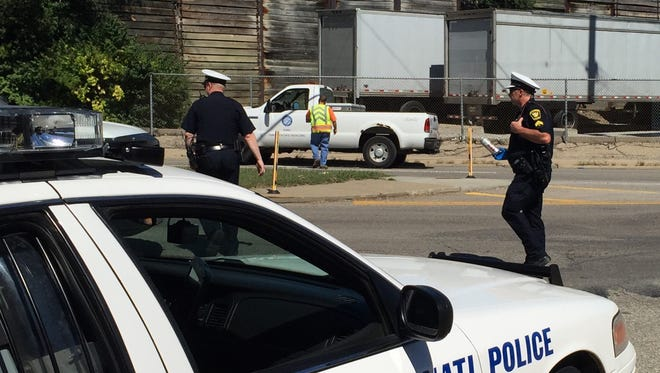A member of the Cincinnati Police Department removes a beer can from the vehicle at the scene.