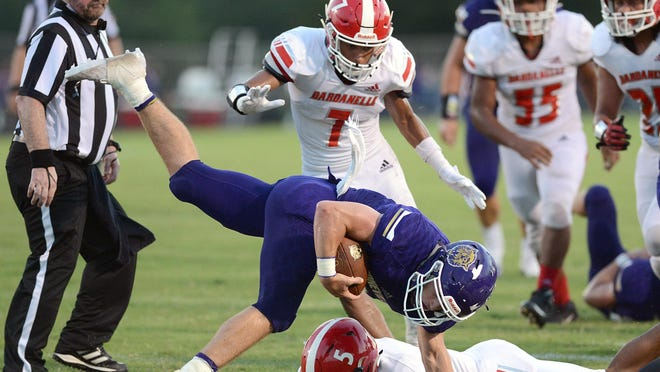 Booneville quarterback Randon Ray, center, breaks a tackle attempt by Dardanelle's Marteez Jackson (5), keeping his balance, and goes 19 yards for a second quarter touchdown on Friday in Booneville.