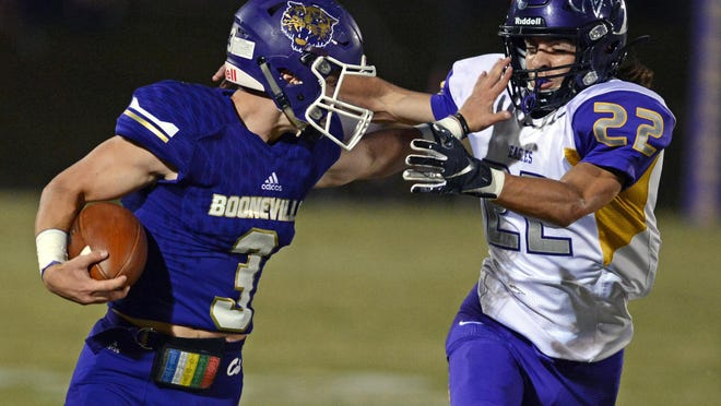 Booneville quarterback Randon Ray fends off Mayflower's J.T. Colvin for a big gain in the first quarter on Friday in Booneville. Booneville won the game 40-7.
