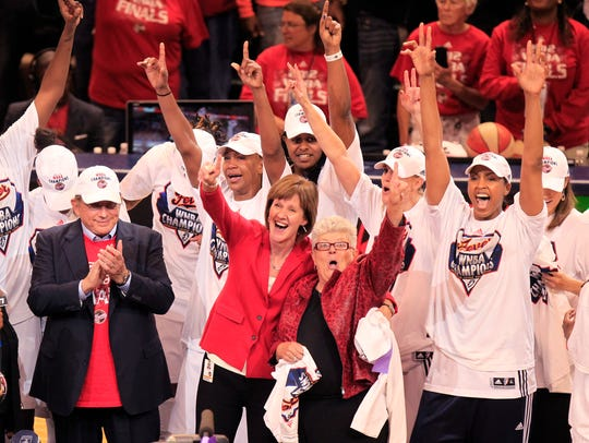 The Indiana Fever, including owner Herb Simon, left, COO Kelly Krauskopf, and coach Lin Dunn celebrate winning a WNBA title with an 87-78 win over the Lynx.