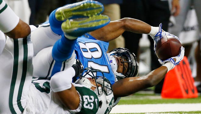 Lions wide receiver Ryan Broyles pulls in a pass while defended by Jets cornerback Dexter McDougle during the first half Thursday at Ford Field.