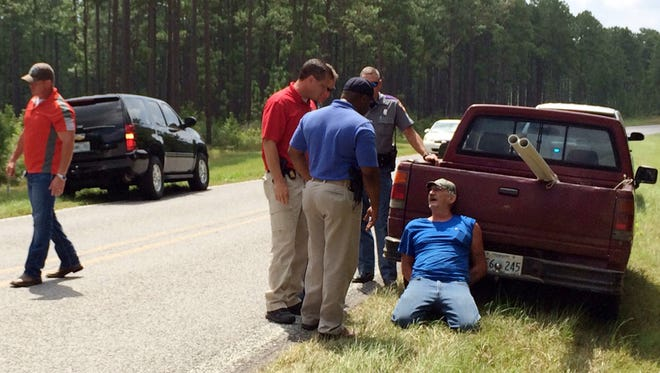 Mississippi Bureau of Investigation agents and state troopers detain a person of interest, right, after shots were reportedly fired Aug. 5, 2015, a second consecutive day, near Camp Shelby, a military training facility south of Hattiesburg, Miss.