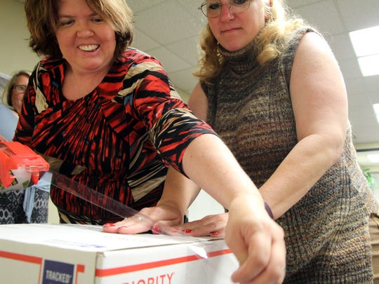 Tassy Mannis, left, and Sheila Kaiser pack boxes to send overseas to Navy sailors.
